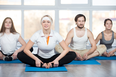 Fitness, stretching practice, group of four beautiful happy fit young people working out in sports club, doing Butterfly Pose for inner thighs, groins, and knees on blue mats in class