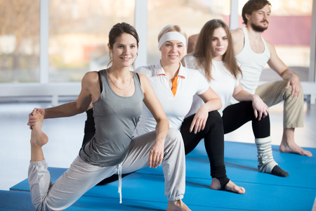 quadriceps: Fitness practice, group of four beautiful happy fit young people working out in sports club, doing warming up exercises, low lunges, Kneeling Quadriceps Stretch with Raised Foot on blue mats