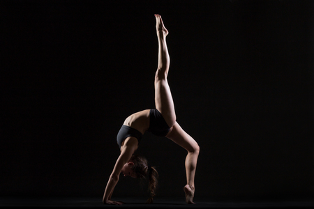 pada: Beautiful cool young fit woman in sportswear doing sport exercise, backbend, One-legged Upward Bow (Wheel) Posture, Eka Pada Urdhva Dhanurasana, full length, side view, studio shot, black background Stock Photo