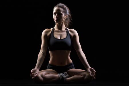 sukhasana: Beautiful serene cool young fit woman in sportswear practicing yoga, sitting in Sukhasana, Easy Posture, asana for meditation, pranayama, full length, front view, studio image, black background