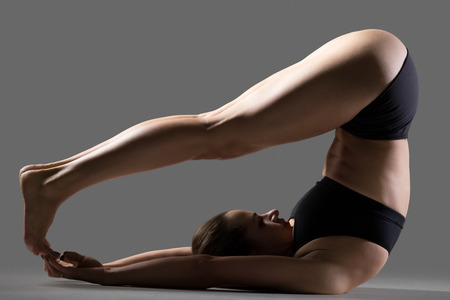 asana: Beautiful young fit woman in sportswear shorts doing sport exercises, variation of Halasana, Plough (Plow) posture, Yin Yoga Snail Pose, full length, side view, studio image on gray background