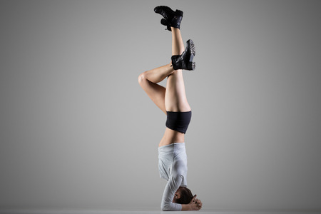 shirshasana: Cool attractive young fit woman doing sports training, variation of supported headstand posture, salamba sirsasana with crossed legs, full length, side view, studio shot on gray background