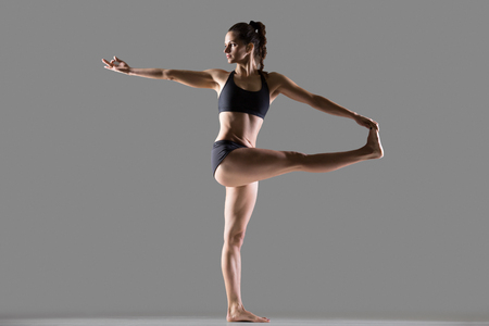 revolved: Portrait of beautiful young fit woman in sportswear doing sport exercise, Parivrtta Hasta Padangusthasana, Revolved Hand to Big Toe posture, full length, studio image, gray background