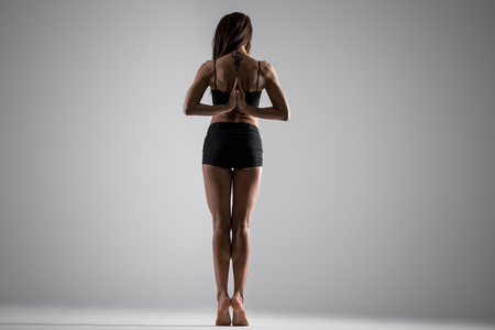 anjali: Beautiful young fit woman in sportswear doing exercises for spine, shoulders, wrists, standing on tip toes, holding Namaste gesture behind the back, full length, rear view, studio, gray background