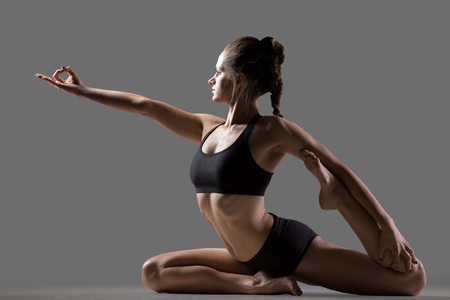 estiramientos: Retrato de la mujer joven del ajuste en ropa deportiva haciendo ejercicio de stretching, sentado en Eka Pada Rajakapotasana, sirena o con una sola pierna Rey Pigeon postura, estudio, fondo gris Foto de archivo