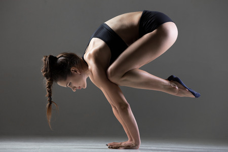 crane: Beautiful young fit woman doing sport exercises, handstand yoga asana, Crane (Crow) Posture, Bakasana (Kakasana), full length, side view, studio shot on gray background