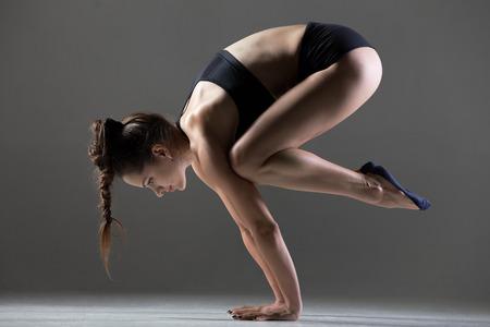 cuervo: ejercicios de deporte hermosas j�venes aptos mujer haciendo parada de manos, asanas de yoga, Crane (Crow) Postura, Bakasana (Kakasana), longitud total, vista lateral, tiro del estudio sobre fondo gris Foto de archivo