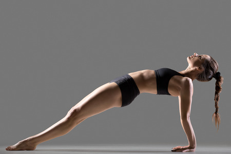 Portrait of beautiful young fit woman in sportswear shorts doing sport exercise, Purvottanasana, Upward Plank posture, shoulders, chest, ankles, arms, wrists, abs, studio image, gray background Stock Photo