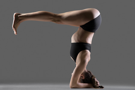 shirshasana: Beautiful young fit woman doing sport exercises, variation of supported headstand asana, salamba sirsasana posture with legs bent at right angle, full length, side view, studio shot on gray background Stock Photo