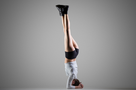 headstand: Cool attractive young fit woman doing sports training, variation of supported headstand posture, Parsva Sirsasana, full length, side view, studio shot on gray background