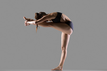 hasta: Beautiful young fit woman in sportswear doing sport exercise, bending in variation of Utthita Hasta Padangusthasana, Dandayamana-Janushirasana, Standing Head to Knee Bikram posture, studio