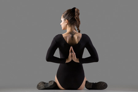 Cool attractive slim young woman doing sports training, warming up, sitting in variation of Gomukhasana, Cow Face Posture with hands in Namaste behind the back, rear view, studio, gray background Banque d'images