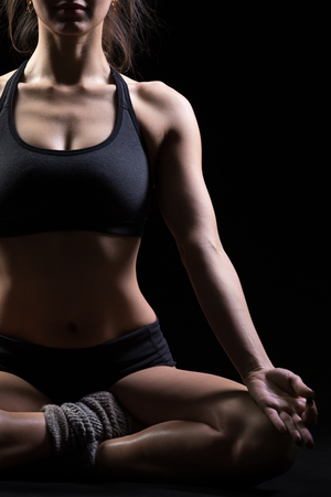 easy: Beautiful cool young fit woman in sportswear practicing yoga, sitting in Sukhasana, Easy Posture, meditating, breathing, front view, studio, black background, close up