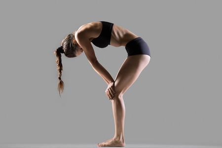 pranayama: Portrait of beautiful young fit woman doing sport exercises, practicing pranayama techniques, Upward Abdominal Lock, Uddiyana Bandha posture, full length, side view, studio image on gray background
