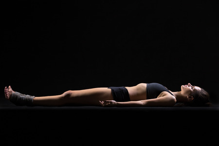 body posture: Beautiful cool young fit woman in sportswear lying in Shavasana (Savasana, Corpse or Dead Body Posture), resting after practice, meditating, breathing, side view, studio, black background