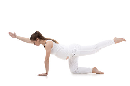 Full length portrait of young pregnant fitness model in sportswear doing yoga, pilates training, balance exercise bird dog, kneeling opposite arm and leg extension, white background, studio, isolated