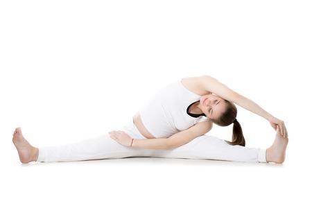 waiting posture: Full length portrait of happy young pregnant fitness model in sportswear, doing yoga, pilates training, Wide-Angle Seated Forward Bend pose, Upavishtha Konasana, white background, studio, isolated