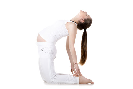 waiting posture: Full length portrait of young pregnant fitness model in sportswear doing yoga or pilates training, warming up, bending in Ustrasana, Camel Pose, white background, studio, isolated