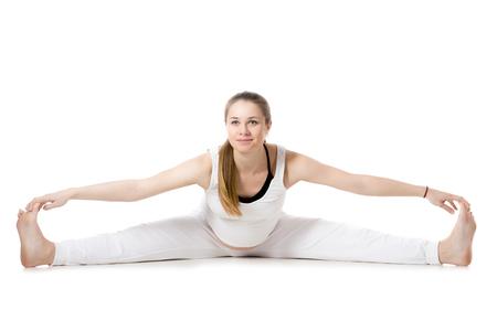 waiting posture: Full length portrait of smiling young pregnant fitness model in sportswear, doing yoga, pilates training, Wide-Angle Seated Forward Bend pose, Upavishtha Konasana, white background, studio, isolated Stock Photo