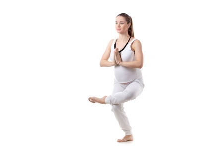 eka: Full length portrait of young pregnant fitness model in white sportswear doing yoga or pilates training, Eka Pada Utkatasana, One-legged Chair Pose, white background, studio shot, isolated