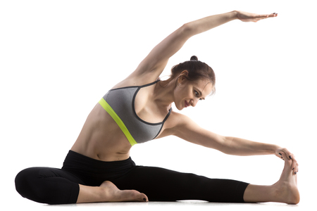 janu: Portrait of sporty fit happy beautiful young woman in sportswear bra and black pants working out, doing Revolved Head to Knee pose, Parivritta Janu Sirsasana, studio full length, white background