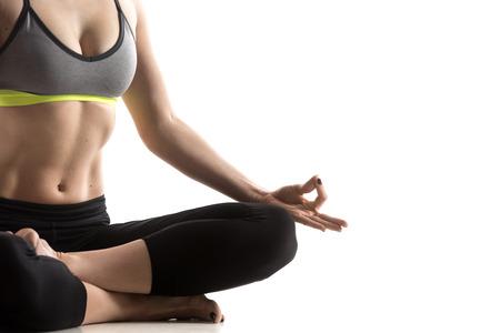 gymnastique: Sporty ajustement belle jeune femme en tenue de sport soutien-gorge et pantalon noir travaillant, assis dans un feu de bois pose, Carré Posture pour les hanches et les aines, studio gros plan, isolé, fond blanc