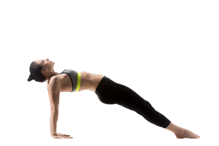 reverse: Portrait of sporty beautiful young brunette woman in sportswear bra and black pants working out, doing Purvottanasana, Reverse Plank Pose, studio full length, isolated shot on white background