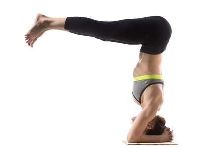 headstand: Sporty fit beautiful young brunette woman in sportswear bra and black pants working out, doing Headstand Half Fold pose, Urdhva Dandasana, studio full length, isolated, white background Stock Photo