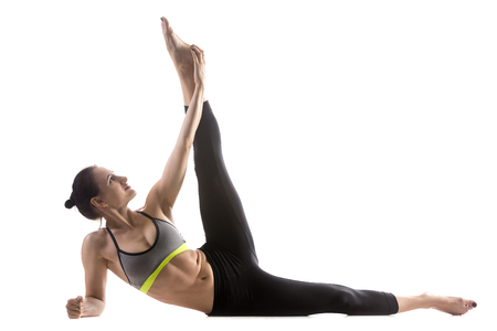 life extension: Sporty fit beautiful young woman in sportswear bra and black pants working out, doing Anantasana, Side-Reclining Leg Lift pose, Sleeping Vishnu posture, studio full length, isolated, white background