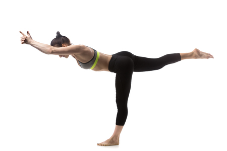 barefoot people: Sporty beautiful young brunette woman in sportswear bra and black pants working out, Warrior III posture (Virabhadrasana 3), Balancing Stick Pose, studio full length, isolated, white background Stock Photo