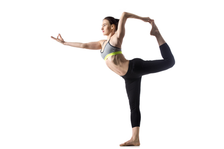 life extension: Sporty fit beautiful young brunette woman in sportswear bra and black pants working out, doing Natarajasana, Lord of the Dance pose, studio full length, isolated, white background