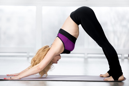 keeping fit: Fitness, stretching workout, blond attractive mature woman working out in sports club, keeping fit, doing downward-facing dog pose, adho mukha svanasana in class, full length Stock Photo