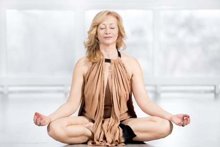 closed club: Fitness, stretching practice, blond attractive happy mature woman in golden outfit working out in sports club, sitting cross-legged, in Easy Posture in class, meditating with closed eyes, full length