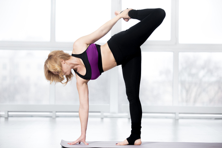 chandrasana: Fitness, stretching workout, attractive mature woman working out in sports club, keeping fit, doing balance exercise, variation of ardha chandrasana posture, Half Moon Pose in class, full length