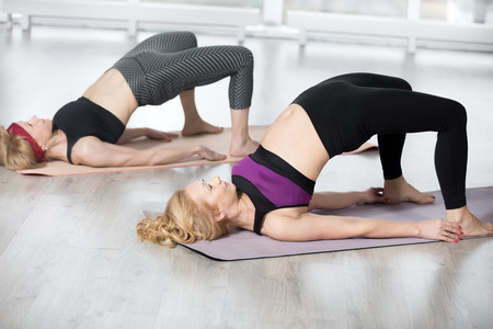 dwi: Fitness, stretching practice, group of two attractive fit mature women working out in sports club, warming up, doing backbend, Setu Bandhasana Pose, shoulder bridge exercise in class, full length