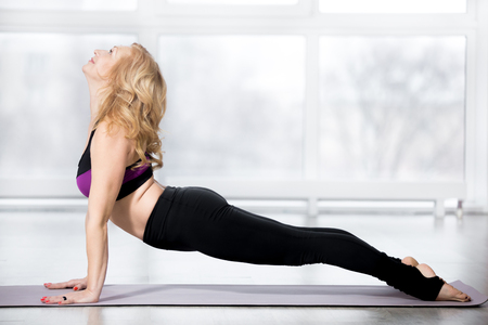 keeping fit: Fitness, stretching workout, blond attractive smiling mature woman working out in sports club, keeping fit, doing urdhva mukha shvanasana (upward facing dog pose) in class, full length