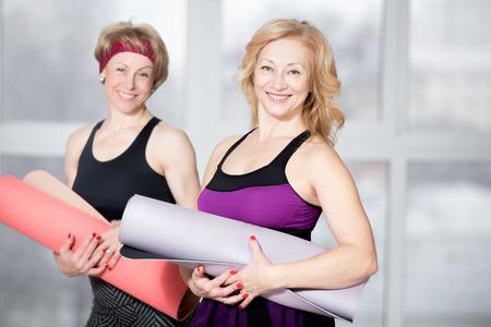 Indoor portret van de groep van twee vrolijke aantrekkelijke fit senior vrouwen poseren met fitness matten, werken in de sportclub de klas, gelukkig lachend, kijkend naar de camera met een vriendelijke uitdrukking Stockfoto