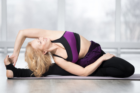 janu: Fitness, stretching workout, attractive mature happy woman in violet sportswear working out in sports club, keeping fit, doing Revolved Head to Knee pose, Parivrtta Janu Sirsasana posture in class Stock Photo