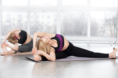 life extension: Fitness, stretching practice, group of two attractive fit mature women working out in sports club, doing Wide-Angle Seated Forward Bend pose variation, Parshva Upavistha Konasana in class, full length