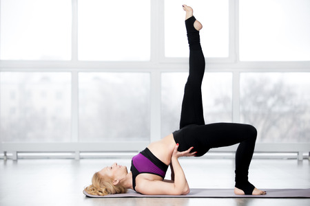 keeping fit: Fitness, stretching workout, attractive mature woman in violet sportswear working out in sports club, keeping fit, doing backbend pose, one-legged shoulder bridge exercise in class, full length