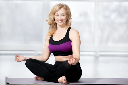 keeping fit: Fitness, stretching practice, blond attractive smiling mature woman working out in sports club, keeping fit, sitting cross-legged, in Easy (Pleasant Posture) on meditation session in class, full length
