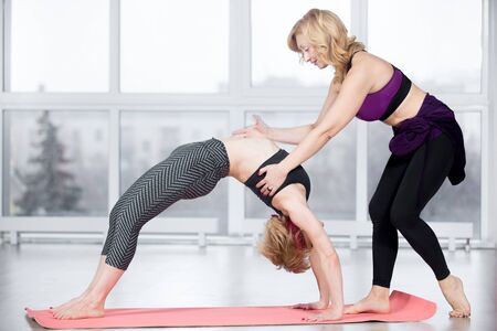 dhanurasana: Fitness, stretching practice, group of two attractive smiling fit mature women working out in sports center, instructor helping female student to do exercise bridge, Upward Bow (Wheel) Pose in class Stock Photo