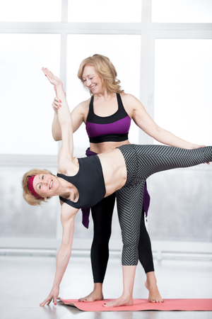 chandrasana: Fitness, stretching practice, group of two attractive fit mature women working out in sports center, instructor helping female student to do asana Ardha Chandrasana (Half Moon Pose) in class