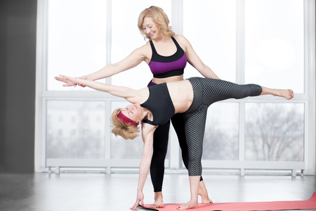 chandrasana: Fitness, stretching practice, group of two attractive fit senior women working out in sports club, instructor helping female student to do asana Ardha Chandrasana (Half Moon Pose) in class