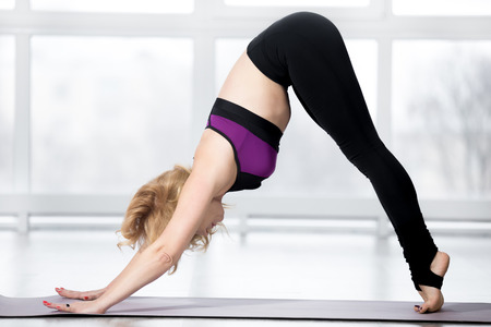 tiptoes: Fitness, stretching workout, attractive mature woman working out in sports club, keeping fit, doing downward-facing dog pose on tiptoes, variation of adho mukha svanasana in class, full length