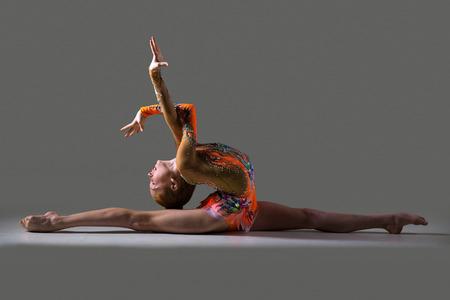 life extension: Beautiful gymnast athlete teenage girl wearing dancer colorful leotard working out, dancing, posing, sitting in splits, doing backbend art gymnastics exercise, studio, dark background Stock Photo