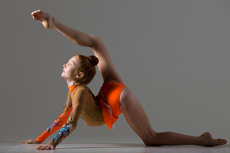 gymnast: Attractive gymnast athlete teenage girl wearing dancer colorful leotard working out, dancing, posing, doing backbend, acrobatic exercise, studio, dark background