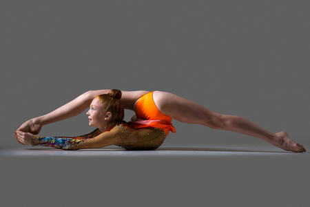 straddle: Beautiful gymnast athlete teenage girl wearing dancer colorful leotard working out, dancing, posing, doing splits with backbend, one-legged acrobatic exercise, studio, dark background