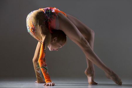 life extension: Beautiful gymnast athlete teenage girl wearing dancer colorful leotard working out, dancing, posing, doing backbend, bridge, art gymnastics exercise, studio, dark background Stock Photo