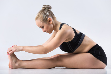 to bend: Sporty beautiful young woman practicing yoga, doing easy variation of seated forward bend pose, paschimothanasana, working out wearing black sportswear, studio, full length